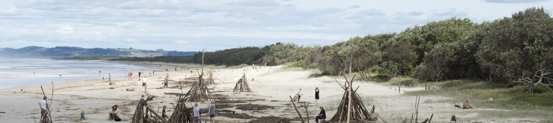 Kids and adults building teepees from driftwood on the beach