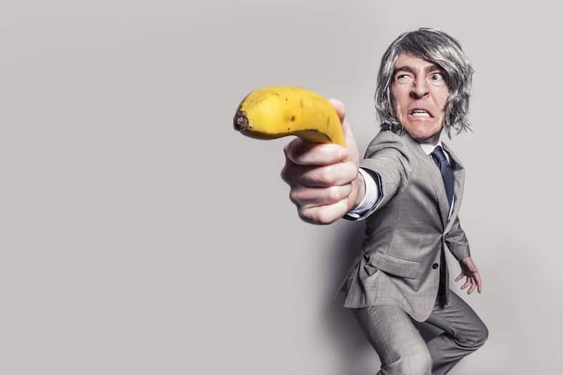Crazy man in grey suit holding banana like a gun