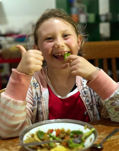 Girl eating broccoli and giving the thumbs up